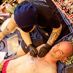 Manchester, UK - 4 August 2012: an artist creates a new tattoo during the Manchester Tattoo Show, one of the most popular conventions of the UK tattoo community.