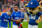 Alfredo Morelos (#20) of Rangers FC carries mascot Lucas Rae-Shreeman (6 years) onto the field before the Ladbrokes Scottish Premiership match between Rangers FC and Heart of Midlothian FC at Ibrox Park, Glasgow, Scotland on 1 December 2019.