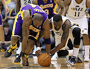 Los Angeles Lakers shooting guard Kobe Bryant, left, and Utah Jazz small forward Josh Howard, right, go after a loose ball during the second half of an NBA basketball game, Saturday, Feb. 4, 2012, in Salt Lake City. The Jazz beat the Lakers 96-87. (AP Photo/Colin E Braley).