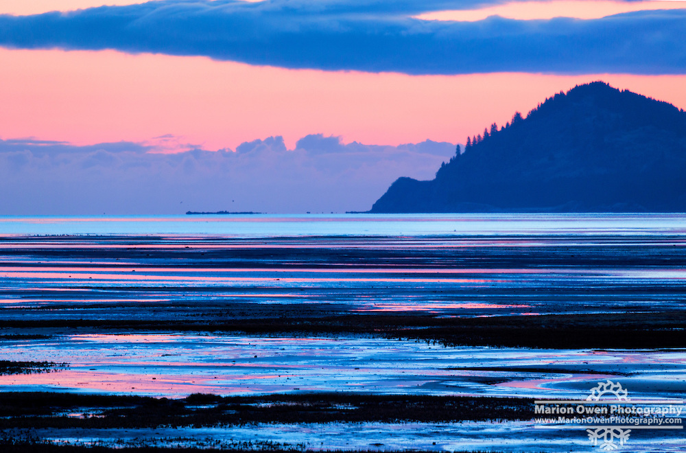 Pink sunrise and low tide create striped landscape near Kodiak, Alaska