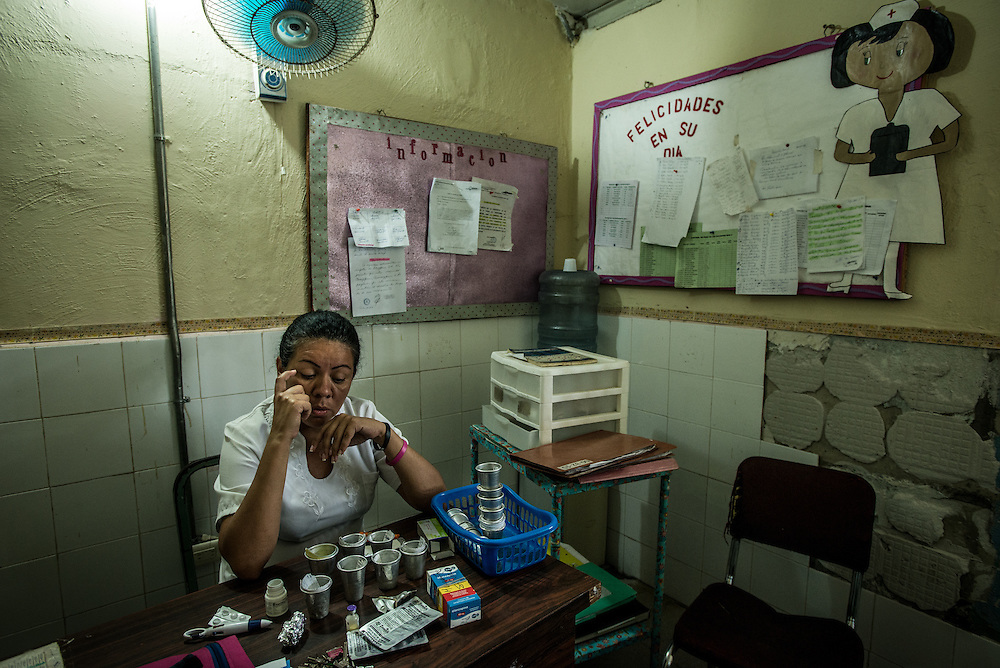 BARQUISIMETO, VENEZUELA - AUGUST 24, 2016: A nurse tries to decide which patients will receive the limited number of pills on hand, and which will go without. The hospital has not employed a psychiatrist in over two years, so even though they are not doctors, the nursing staff find themselves responsible for doing a psychiatrist's work - they make decisions about how to medicate patients - modifying doses and swapping one patient's pills to give to another, who might be more unstable and need them more. They reference medical files from two years ago when a licensed psychiatrist was on staff - all written by hand and kept in paper folders. They use a mix of the old treatment plans from two years ago, plus their own observations of the patient, and modify treatments and care based on years of learning from trial and error.   The economic crisis that has left Venezuela with little hard currency has also severely affected its public health system, crippling hospitals like El Pampero Psychiatric Hospital by leaving it without the resources it needs to take care of patients living there. Drugs used to combat bipolar disorder, epilepsy, schizoaffective disorder and chronic anxiety are now in short supply, as are numerous sedatives and tranquilizers needed to care for patients. When a patient loses control, often the only thing they can do is lock them in an isolation cell to prevent them from hurting themselves, other patients and members of the staff.  PHOTO: Meridith Kohut for The New York Times