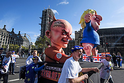 © Licensed to London News Pictures. 19/10/2019. London, UK. An effigy of DOMINIC CUMMINGS using British Prime Minister BORIS JOHNSON as a puppet is pushed past The Houses of Parliament in Westminster, London on the day that Parliament will vote on a new agreement between UK government and the EU over Brexit. Parliament is sitting on a Saturday for the first time since 1982. Photo credit: Ben Cawthra/LNP