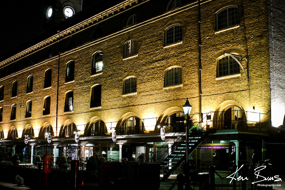 A night photo of plush apartments that have been converted from old warehouses in the expensive St. Katharine Docks in London. The docks are in the London Borough of Tower Hamlets and were originally part of the Port of London, Docklands.