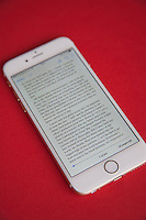 Reading an ebook on a Gold and white Apple iPhone 6 against a red background
