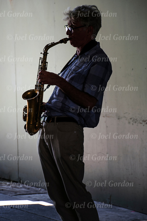 Silhouette of street musician playing the saxophone<br />