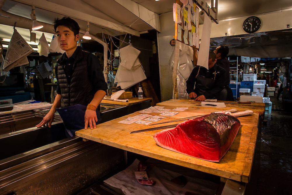A tuna seller waits for some customers near a piece of red tuna.
