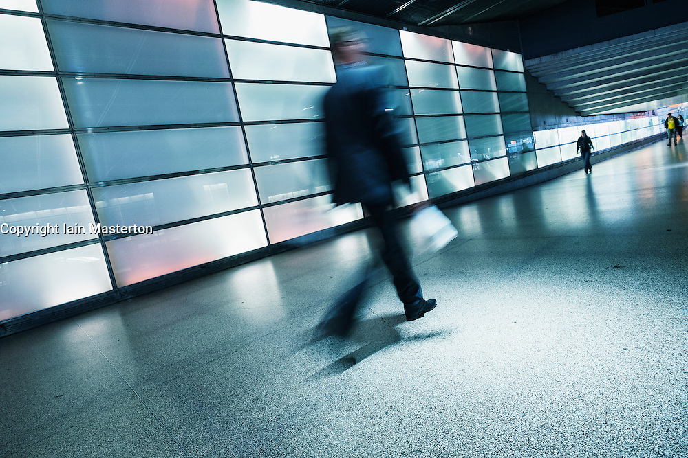 Passengers walking in illuminated passageway in Interior of Potsdamer Platz railway station in Berlin Germany