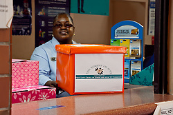 "Prudencia Freeman stands behind the ""Tiny Tokens of Hope"" donation box at the Post Office on Main St.  First Lady Mrs. Cecile de Jongh is holding the toiletry drive to help provide care packages to the homeless in the USVI community."