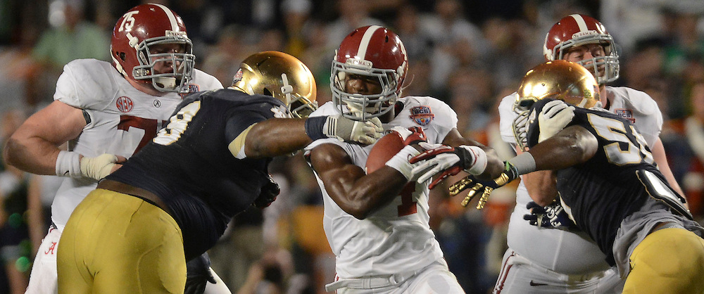Daily Photo by Gary Cosby Jr.   Notre Dame nose guard Louis Nix III pulls down Alabama running back T.J. Yeldon (4) during the first half of the BCS National Championship Game in Sun Life Stadium Monday, January 7, 2013.