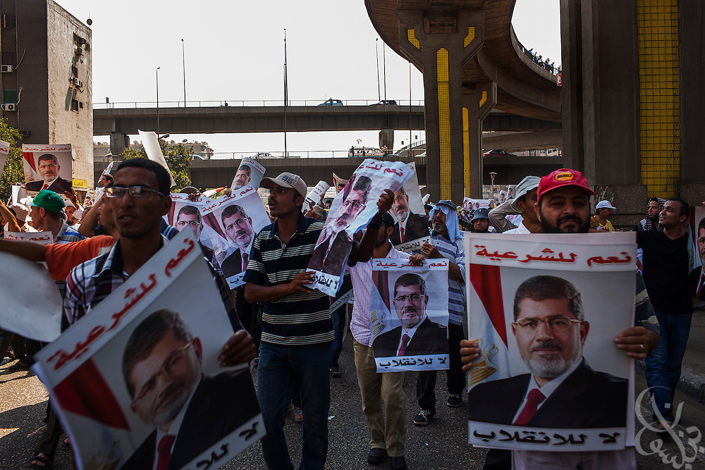 Supporters of deposed Egyptian president Mohamed Morsi march with posters of the ex-leader as they make there way to continuing large scale demonstrations and sit-in around the Rabaah al-Adawia mosque and square in the Nasr City district of Cairo Friday July 26, 2013.  The supporters are demanding the reinstatement of the deposed President and are opposed to the EGyptian military, which they say has undertaken an undemocratic coup.