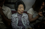 Matriarch with gloves and red lipstick on the train in Tokyo.  Japan.