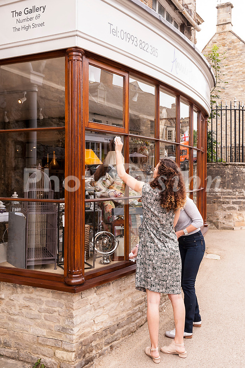 2 women clean the shop window of the Gallery shop store in Burford , Oxfordshire , England , Britain , U