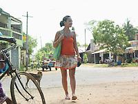 Young woman walking dirt road smiling