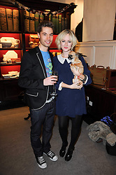 Actress JESSICA DOLMAN holding her dog Missy and MARK SENIOR at a party to celebrate the publication of Dogs in Vogue by Judith Watt held at James Purdey & Sons, Audley House, 57-58 South Audley Street, London W1 on 3rd December 2009.