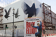 A bus advert for the musical Billy Elliott drives past a construction hoarding featuring giant birds in flight spreading wings.