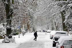 © Licensed to London News Pictures. 21/01/2013, London, UK. A man walks across a snow covered street in Croydon, South London, Monday, Jan. 21, 2013. Britain is continue affect by cold weather and snow. Photo credit : Sang Tan/LNP