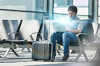 Portrait of man working with his laptop while waiting for boarding in airport