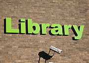 Green lettering sign for Library with CCTV camera