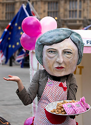 © Licensed to London News Pictures. 10/12/2018. London, UK. A person dressed as British Prime Minister Theresa May gives away fudge outside the Houses of Parliament, as part of a photocall hosted by Avaaz. Tomorrow MPs will vote on May's withdrawal deal. Photo credit : Tom Nicholson/LNP