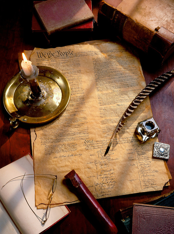 A desktop scene depicting the signing of the American Declaration of Independence with quill pen and a candle
