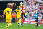 Charlie Wyke (#9) of Sunderland AFC and Nesta Guinness-Walker (#18) of AFC Wimbledon challenge for a header during the EFL Sky Bet League 1 match between Sunderland and AFC Wimbledon at the Stadium Of Light, Sunderland, England on 24 August 2019.