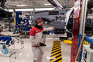 CASSINO, ITALY - NOVEMBER 24: An employee works in the Assembly Lines where they assemble the Alfa Romeo Giulia in the Cassino Assembly Plant FCA Group. In this area it takes place manual work this is why new workstations designed to reduce fatigue and improve ergonomics have been introduced on November 24, 2016 in Cassino, Italy.