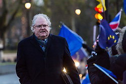 London, December 11 2017. As MPs prepare to debate a petition calling for a referendum on the final Brxit deal, Stop Brexit dozens of protesters demonstrate outside Parliament at Old Palace Yard. PICTURED: Staunch Brexit supporter Lord Digby Jones walks past the protest on his way to hail a cab. © Paul Davey