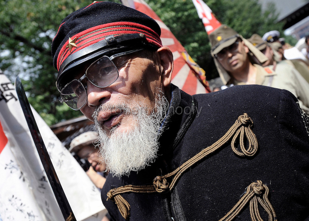 Dressed in Edo-period military garb, Hakugaku Kuribayashi, 80, leads a march to pray during a events to commemorate the anniversary of the end of World War II at Yasukuni Shrine in Tokyo, Japan on 15 Aug. 2008. Wartime prime minister Hideki Tojo - who ordered the attack on Peal Harbor and was charged and hanged as a war criminal after World War II, is enshrined inside the controversial Yasukuni Shrine together with 13 other convicted war criminals, a fact that still angers citizens in China and South Korea, both of which fell vicim to Japan's wartime activities. Aug 15. is the anniversary of Japan's surrender in World War II and 100s of thousands of pilgrims from around the country visit the shrine..Photographer: Robert Gilhooly