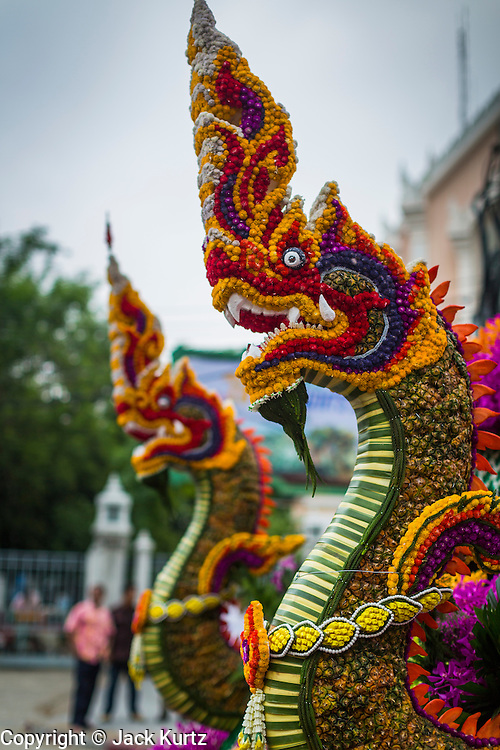 "12 APRIL 2014 - BANGKOK, THAILAND:  Floral ""nagas"" on a Songkran parade float in Bangkok. A ""naga"" is a mythical serpent that protects temples. The Phra Buddha Sihing, a revered statue of the Buddha, is carried by truck through the streets of Bangkok so people can make offerings and bathe it in scented oils. Songkran is celebrated in Thailand as the traditional New Year's from 13 to 16 April. The date of the festival was originally set by astrological calculation, but it is now fixed. The traditional Thai New Year has been a national holiday since 1940, when Thailand moved the first day of the year to January 1. The first day of the holiday period is generally the most devout and many people go to temples to make merit and offer prayers for the new year.      PHOTO BY JACK KURTZ"