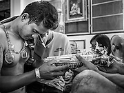 """14 MARCH 2014 - NAKHON CHAI SI, NAKHON PATHOM, THAILAND: A man getting a sak yant tattoo makes an offering to the tattooist at Wat Bang Phra. Wat Bang Phra is the best known """"Sak Yant"""" tattoo temple in Thailand. It's located in Nakhon Pathom province, about 40 miles from Bangkok. The tattoos are given with hollow stainless steel needles and are thought to possess magical powers of protection. The tattoos, which are given by Buddhist monks, are popular with soldiers, policeman and gangsters, people who generally live in harm's way. The tattoo must be activated to remain powerful and the annual Wai Khru Ceremony (tattoo festival) at the temple draws thousands of devotees who come to the temple to activate or renew the tattoos. People go into trance like states and then assume the personality of their tattoo, so people with tiger tattoos assume the personality of a tiger, people with monkey tattoos take on the personality of a monkey and so on. In recent years the tattoo festival has become popular with tourists who make the trip to Nakorn Pathom province to see a side of """"exotic"""" Thailand.   PHOTO BY JACK KURTZ"""