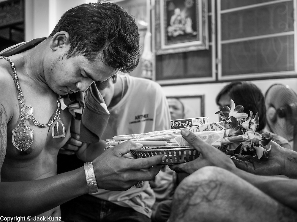 "14 MARCH 2014 - NAKHON CHAI SI, NAKHON PATHOM, THAILAND: A man getting a sak yant tattoo makes an offering to the tattooist at Wat Bang Phra. Wat Bang Phra is the best known ""Sak Yant"" tattoo temple in Thailand. It's located in Nakhon Pathom province, about 40 miles from Bangkok. The tattoos are given with hollow stainless steel needles and are thought to possess magical powers of protection. The tattoos, which are given by Buddhist monks, are popular with soldiers, policeman and gangsters, people who generally live in harm's way. The tattoo must be activated to remain powerful and the annual Wai Khru Ceremony (tattoo festival) at the temple draws thousands of devotees who come to the temple to activate or renew the tattoos. People go into trance like states and then assume the personality of their tattoo, so people with tiger tattoos assume the personality of a tiger, people with monkey tattoos take on the personality of a monkey and so on. In recent years the tattoo festival has become popular with tourists who make the trip to Nakorn Pathom province to see a side of ""exotic"" Thailand.   PHOTO BY JACK KURTZ"