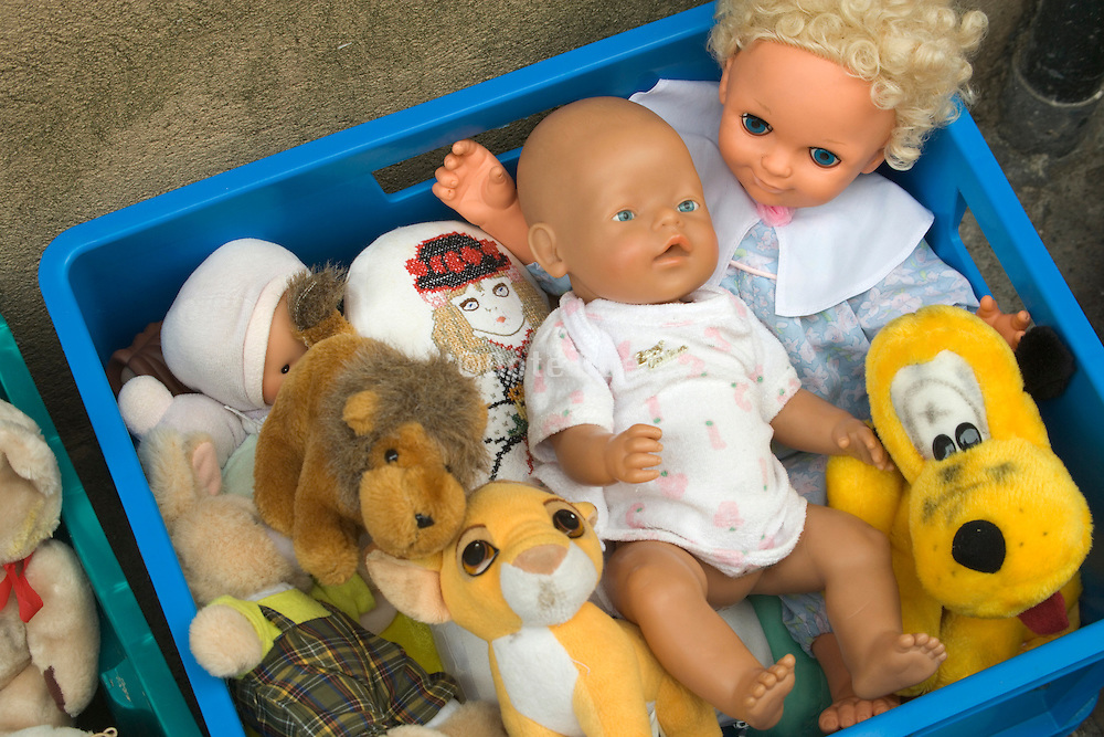 childhood toys stuffed in to a crate and for sale at a flee market