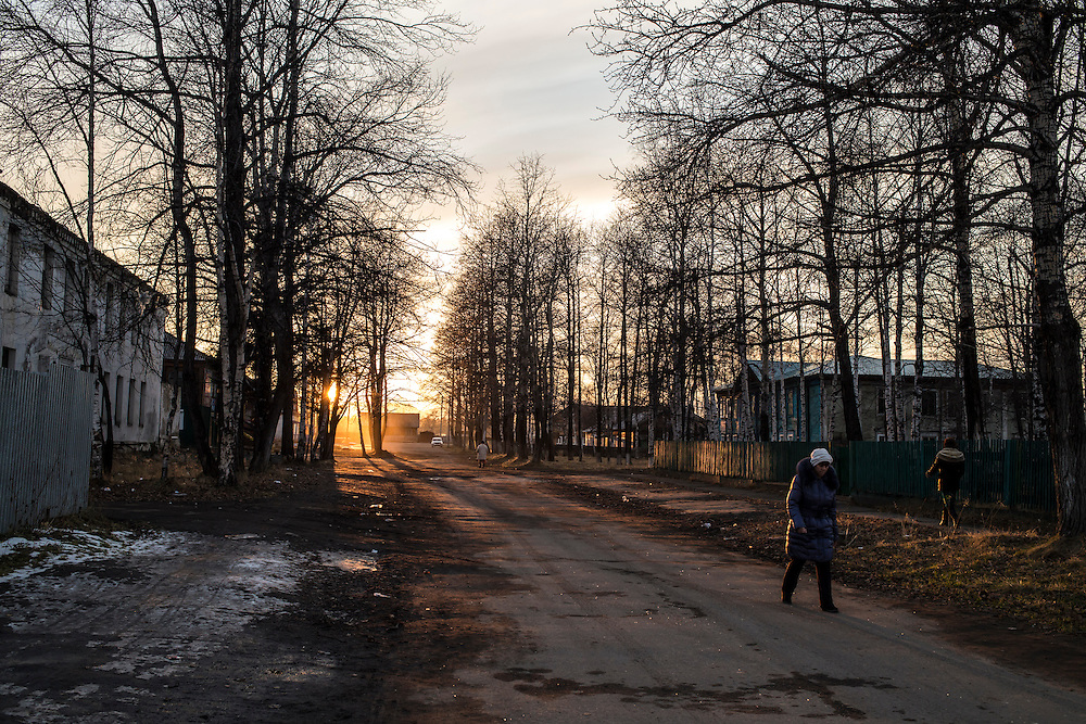 Women walk down the street at sunset on Wednesday, October 23, 2013 in Vydrino, Russia.