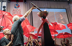 "26 July 2018, Amsterdam, the Netherlands: Demonstrators shout ""shame, shame, shame"" as the Positive Flame, described as a ""torch of inclusion"" is lit at the 2018 International AIDS Conference. The torch is to connect the 2018 conference with the 2020 conference, which is expected to take place in the United States, and the protestors, many of whom are sex workers or are part of other key populations, object because people from key populations as well as other groups, such as Muslims, may have difficilties getting a visa to travel to the United States. ""No conference in the United States, no conference in the United States,"" they continued to chant. The Positive Flame is intended to travel from one International AIDS Conference to the next, and echoes the Olympic Flame that was introduced at the Olympic Games in Amsterdam in 1928."
