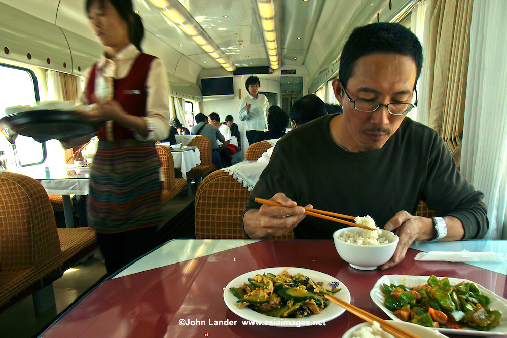 Dining Car on the Tibet Train - The Qinghai-Tibet Railway, the highest rail line in the world, is usually called the Tibet Train.  Its 1,200 miles of tracks traverse 342 miles of permafrost, lots of it at altitudes exceeding 12,000 feet. The end of the line is Lhasa, Tibet. Proponents of the new railway say it will bring economic development to the Tibet and China's hinterlands as Tibet and China's far west lag behind the rest of the country, and rail connectivity promises to be a crucial tool for closing that gap.  Critics say the railway is  a political tool to strategically stitch Tibet into the fabric of China and facilitate the westward migration of ethnic Chinese.  The only thing about the train that everyone agrees on,  the the Tibet  train is an engineering marvel.