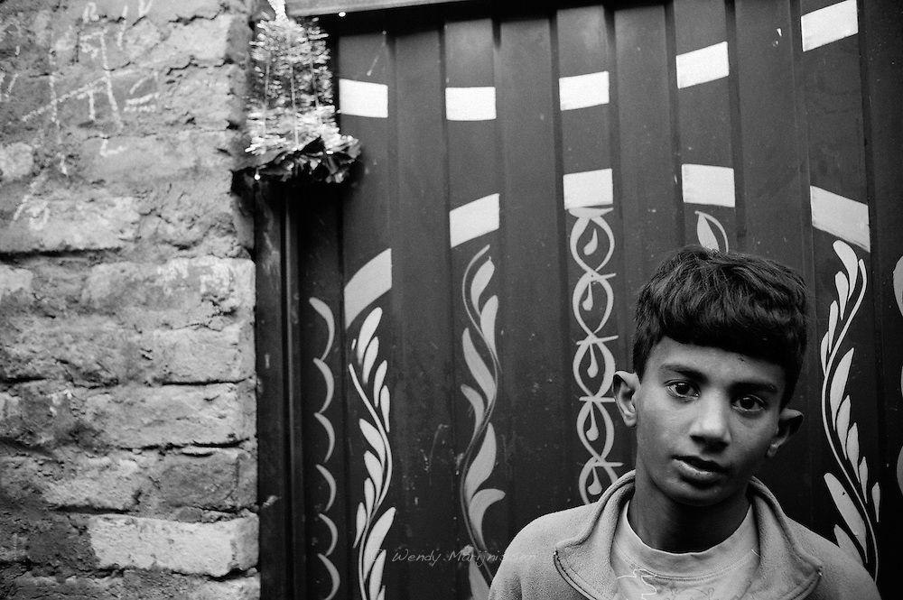 A young boy standing in front of a door that already has a Christmas decoration hanging in preperation of the coming holiday. French colony slum, Islamabad