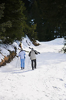 Skiing couple walking down ski slope carrying skis on shoulders back view elevated view