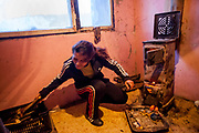 "Milena (mother of four daughters and a son) heating with wood. The family moved into another and final compensatory flat at Lunik IX after their first building (""Hrebenova 34-36"") was demolished by the city of Kosice in August 2014, the second flat was not in a appropriate condition."