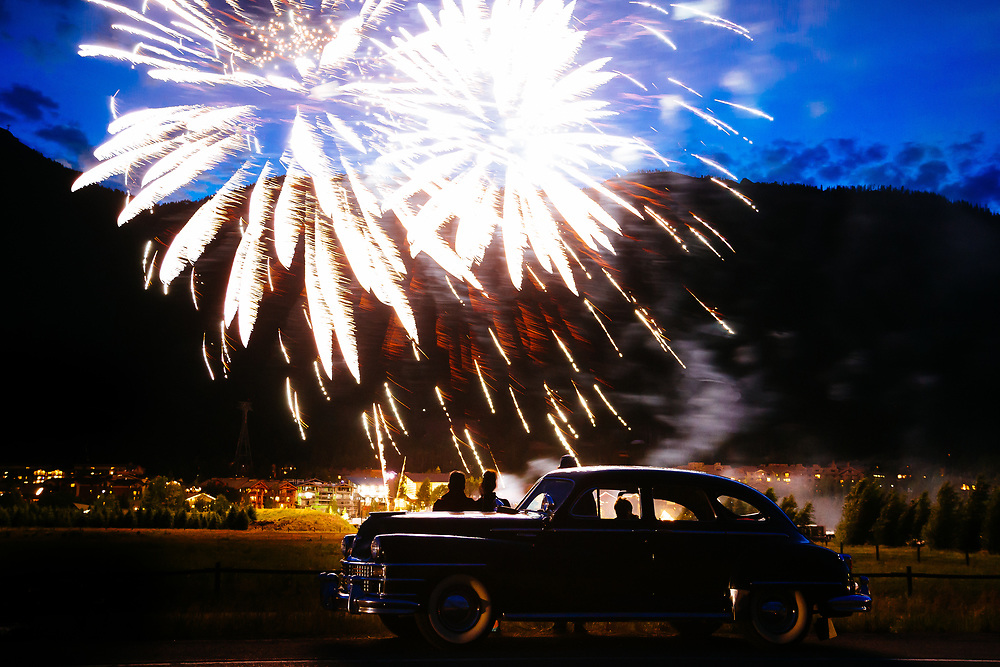Fourth of July fireworks explode beyond the silhouettes of people and a classic car.