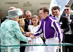Queen Elizabeth II shakes the hand of jockey Ryan Moore after he rode Merchant Navy to victory in the Diamond Jubilee Stakes during day five of Royal Ascot at Ascot Racecourse.