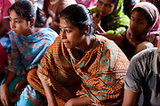 """Nusrat Jahan Popy (16, 2nd from right) speaks during a monthly meeting of a Children's Group in Bhashantek Basti (Slum) in Zon H, Dhaka, Bangladesh on 23rd September 2011. Popy says, """"I feel helpless, not angry (if my parents would try to marry me off). I can do stitching and we want to be allowed to work so that we can earn money to support ourselves in our studies and to rid ourselves of poverty and gain independence."""" The Bhashantek Basti Childrens Group is run by children for children with the facilitation of PLAN Bangladesh and other partner NGOs. Slum children from ages 8 to 17 run the group within their own communities to protect vulnerable children from child related issues such as child marriage. Photo by Suzanne Lee for The Guardian"""