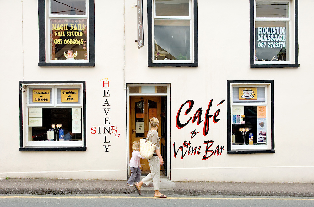 Temptation in the streets of Dingle town, County Kerry, Ireland. Mother, daughter pass the Heavenly Sins cafe wine bar exterior.