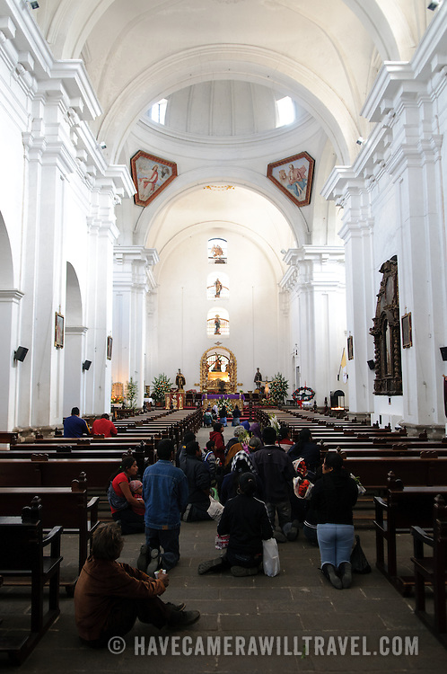 Worshippers make their way on their knees down the aisle of the knave in Iglesia de San Francisco in Antigua, Guatemala.