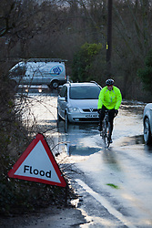 © Licensed to London News Pictures. 01/02/2014. Titchfield, Hampshire, UK. A man riding his bike through flood water from the River Meon, which is out of bank in Titchfield, Hampshire. The flood water caught motorists out, some of which suffered car breakdowns. There is wet and windy weather forecast for the UK today, 1st February 2014. Photo credit : Rob Arnold/LNP