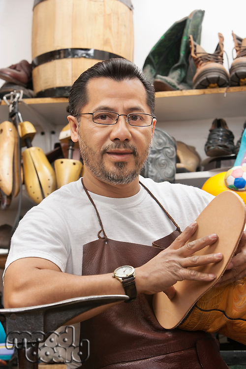 Portrait of a confident cobbler with shoe sole in workshop