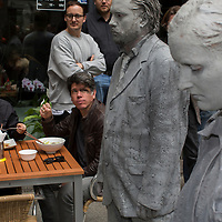 DE, DEUTSCHLAND, Hamburg. 05.07.2017 / Protestaktion 1000 Gestalten: Im Vorfeld des G20-Gipfels findet mitten in der Hamburger City eine Aktion mit lehmverschmierten Gestalten statt, waehrend im Hintergrund Touristen zu Mittag essen.