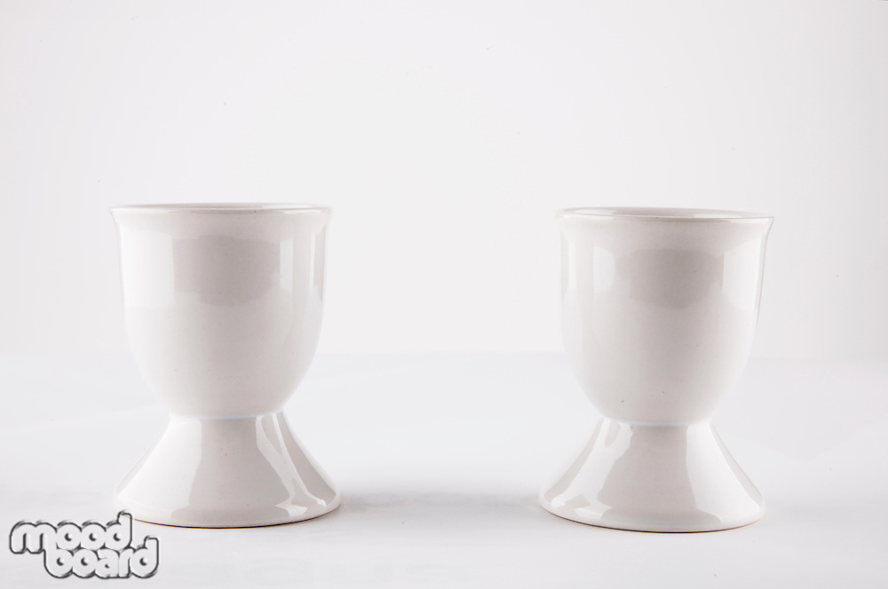 Empty egg cups side by side over white background