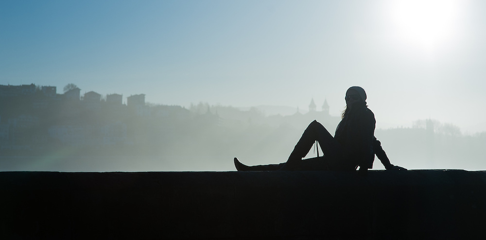 Silhouette of woman sat on balaustrade in San Sebastian (Spain)