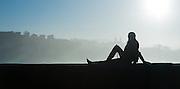 Silhouette of woman sat on balaustrade in San Sebastian (Spain)