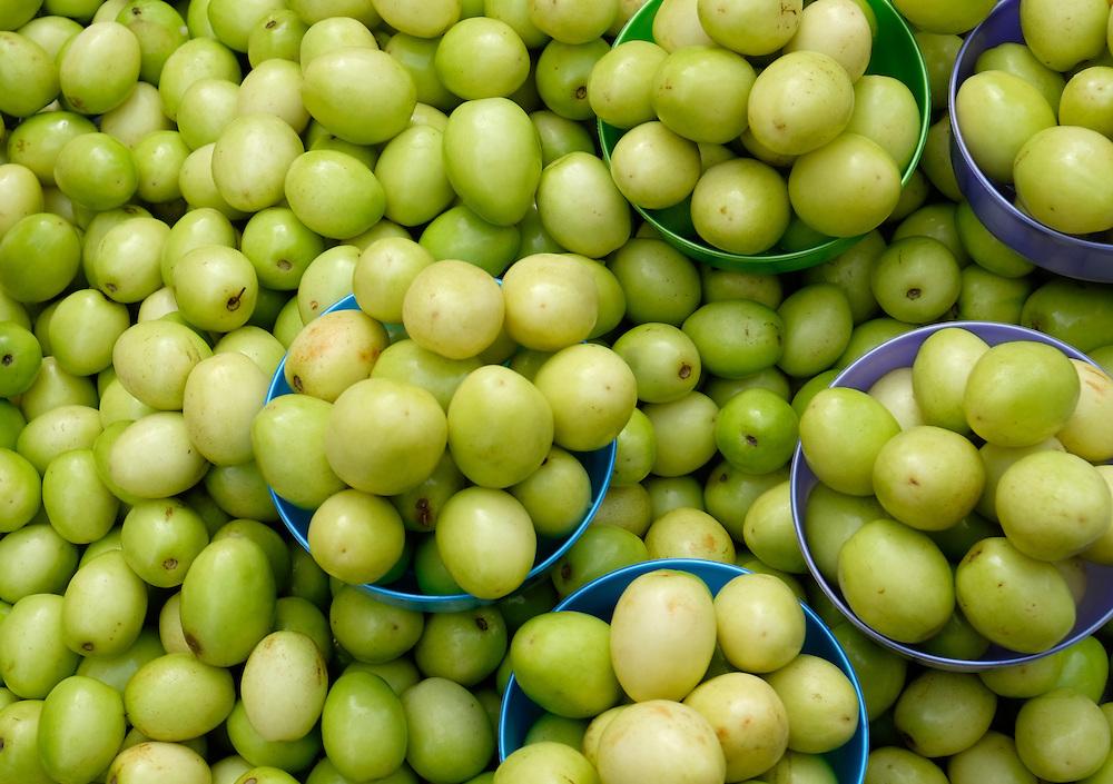 YANGON, MYANMAR - CIRCA DECEMBER 2013: Variety of green tomato in the street market of Yangon.